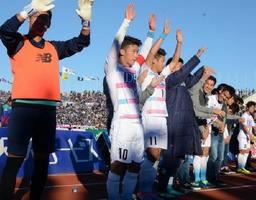 甲府との今季最終戦を1―0で勝利し、サポーターの声援に応える金民友(左)ら鳥栖の選手たち=山梨中銀スタジアム