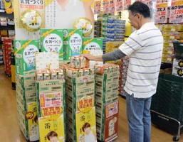県産大麦100%使用の「佐賀づくり」を手に取る男性客=佐賀市南佐賀のあんくるふじや佐賀本店