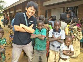 前回の赴任時にマラウイの子どもたちと記念撮影する寺﨑一生さん(左)。JICAシニア海外協力隊員として特産品の開発などを担当した(提供)