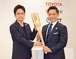 自らがデザインした東京五輪聖火リレーのトーチを披露する吉岡徳仁さん(左)と公式アンバサダーの野村忠宏さん=東京港区の虎ノ門ヒルズ