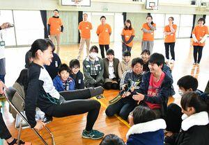義足がどれだけ強力に固定されているか、引っ張って確かめる児童たち。左は講師の山下千絵選手=佐賀市の西与賀小