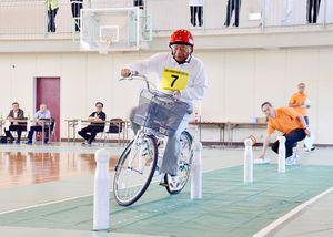 自転車の安全走行テストで、ポールの間を走る杉原辰雄さん=佐賀市の大和勤労者体育センター