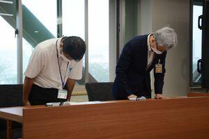 当て逃げ事故を起こした職員の処分について説明し、陳謝する伊東博巳副市長(右)=佐賀市役所