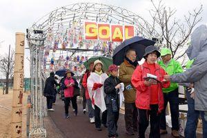 雨の中ゴールし、景品を受け取る参加者=佐賀市兵庫北のトンボの池公園