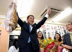 当選が確実となり、支援者から贈られたタイを掲げる峰達郎氏=29日午後10時43分、唐津市町田の事務所