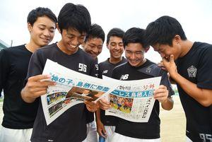 トーレス移籍の号外を読む佐賀北サッカー部の選手たち=佐賀北高校