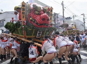 力水を浴びながら山車を激しく揺らす本通町「神楽獅子」の男衆。奥は本町「飛び立つ鷲」=鳥栖市中心街