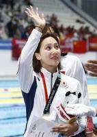 女子200メートル平泳ぎで大会2連覇を達成し、観客の歓声に応える渡部香生子=ジャカルタ(共同)