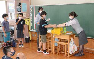 乗客から荷物を預かる作業を体験する児童=有田町の大山小