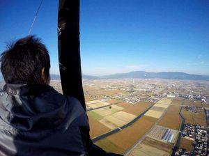 バルーンから佐賀平野を眺める岩本記者。下を見ないように、視線を遠くに向けている。