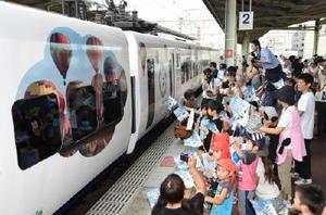 「バルーンかもめ号」の運行開始日。小旗を振る市民らに迎えられた=8月26日、佐賀市のJR佐賀駅