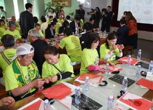 切り紙細工を楽しみ、中国の伝統文化に触れる市民訪問団=中国・大連市の現代博物館