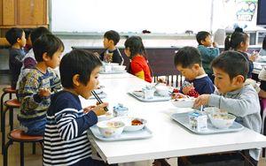 小学校の給食をおいしそうにほおばる園児=有田小
