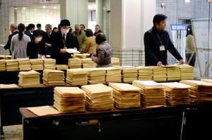 来場者が少なく、受付には配布資料が山積みされたままだった=2月27日、佐賀市文化会館