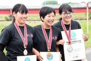 入賞した後輩たちと並ぶ竹永萌夏さん(中央)=唐津市の松浦川ボートハウス
