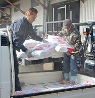 消毒に使う消石灰をトラックに積み込む養鶏農家=多久市のJAさが多久グリーンセンター