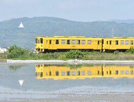 行き交う列車や周りの景色を鏡のように映している田植え前の田んぼ=小城市三日月町