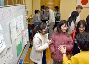 避難所に外国人を受け入れる訓練で、掲示板の前で食事の時間などを確認する参加者=佐賀市本庄町の本庄公民館