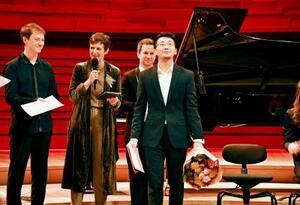 ロン・ティボー・クレスパン国際音楽コンクールの授賞式で、優勝の賞状と花束を受け取ったピアニストの三浦謙司さん(手前)=16日、パリ(共同)