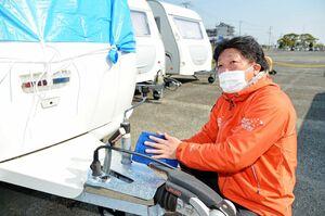 A-PADジャパンのキャンピングトレーラーを点検する菅名紀之さん=鳥栖市の佐賀競馬駐車場