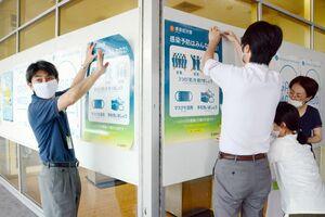 新型コロナウイルス感染予防を啓発するポスターを貼る市職員ら=佐賀市の佐賀駅バスセンター