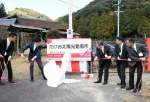 288枚のソーラーパネルを備えた「たけお太陽光発電所」のテープカットを行う野畑社長(左)と小松市長(左から2人目)ら関係者=武雄市武雄町