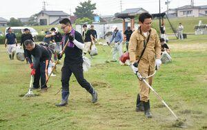 草刈り機で雑草を刈る参加者たち=佐賀市川副町の三重津海軍所跡