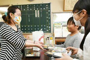 佐賀こども食堂が手作りした弁当を受け取る子ども=佐賀市の勧興公民館