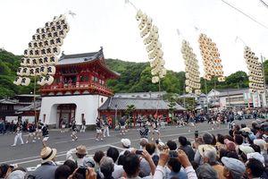 武雄温泉楼門の前で披露される竿燈まつりの妙技=12日午後6時12分、武雄市
