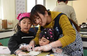 巻き寿司作りを楽しむ親子=神埼市中央公民館