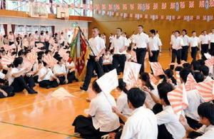 優勝旗を持つ占部主将を先頭に入場する野球部と、拍手で迎える生徒たち=唐津市の早稲田佐賀中学・高校の体育館