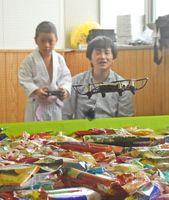 ドローンでお菓子をつり上げる児童=佐賀市商工ビルの市民活動プラザ
