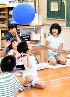 休み時間には「風船バレー」で遊び、夢中になってボールに手を伸ばす園児と児童たち=佐賀市の県立ろう学校