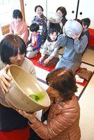 支え合うなどして、大きな茶碗で茶会を楽しむ参加者=唐津市鎮西町の名護屋城茶苑「海月」