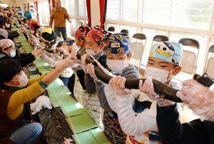 完成した18メートルの手巻きずしを高く持ち上げる児童=佐賀市の嘉瀬小学校