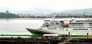 昨年5月、唐津港東港改修第1船として入港した「ぱしふぃっくびいなす」。左奥は唐津城=唐津市東大島町