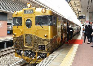 金色に唐草文で装飾された車体が目を引くJR九州のスイーツトレイン「或る列車」。乗車時敷かれるレッドカーペットも豪華な旅気分を浮き立たせる=福岡市のJR博多駅