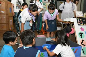 おもちゃの金魚をすくって遊ぶ店で、訪れた子どもたちに説明する児童と夢中になって遊ぶ子どもたち(手前)=佐賀市の白山名店街