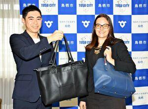 バッグを手にする安武祥太さん(左)とマリーさん=鳥栖市役所