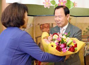 議員から笑顔で花束を受け取る原信義さん=神埼市神埼町の「菊水」