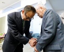 支持者に頭を下げる岡本憲幸さん(左)=唐津市神田の事務所