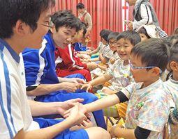高校生によるハンドマッサージを受け、笑顔になる子どもたち=佐賀市駅前中央の「神野こども園」