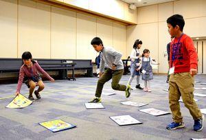 読み上げられた標語に対応した、大きなかるたを取る参加者=唐津市相知町の交流文化センター