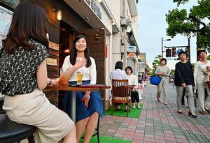 店先のテラス席で飲食を楽しむ女性客=22日午後7時ごろ、佐賀市唐人