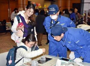 指紋採取の体験をする来場者=佐賀市文化会館