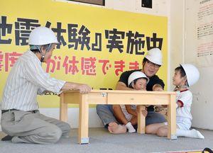 イベント初登場の起震車で、直下型地震を体験する参加者たち=佐賀市のどんどんどんの森