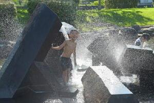 噴水のある池で水遊びをする子どもたち=佐賀市兵庫北の夢咲公園