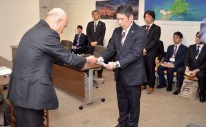 九州電力の山元春義取締役(左)が副島良彦副知事(中央)に玄海原発3号機の蒸気漏れトラブルに関する最終報告書を手渡した=県庁
