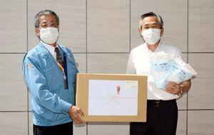 原勝章事務長にマスクを手渡す藤崎鉄浩社長(左)=佐賀市の佐賀整肢学園
