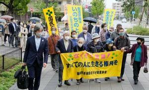 生活保護の基準額引き下げを巡る訴訟の判決で、福岡地裁に入る原告ら=12日午後